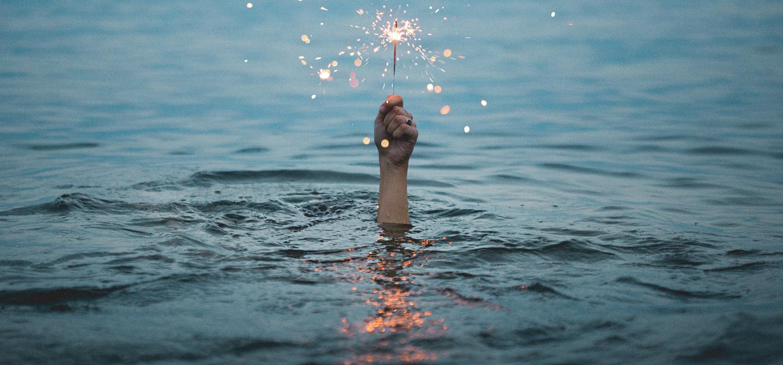 mano con fuego artificial en el mar